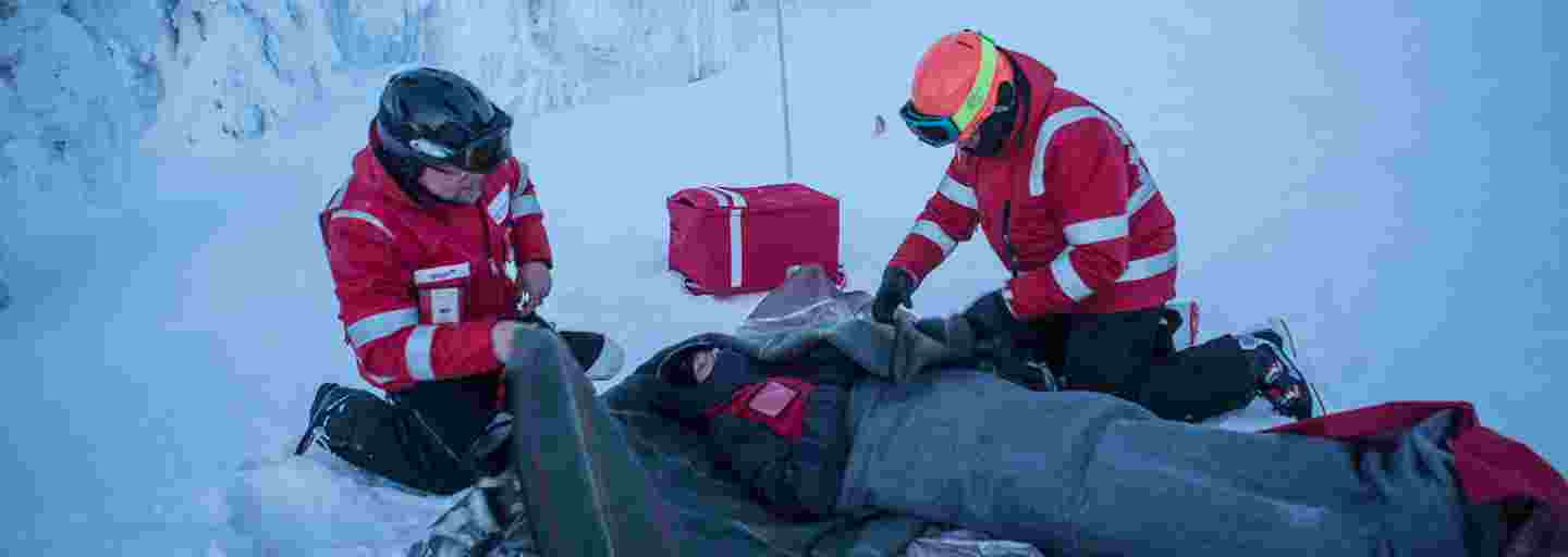 Two Red Cross ski slope volunteers wrapping a blanket around someone lying on the snow at the side of a ski slope.